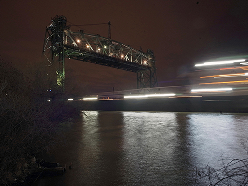 Photo by Michael Loderstedt, a night scene of a large freight boat going under a bridge.
