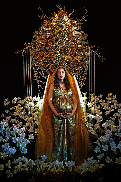 Mr. Gnome, a pregnant woman dressed in gold with lilies surrounding her
