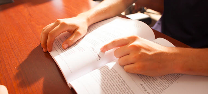 A textbook sits on a table with a student's finger panning it's pages.