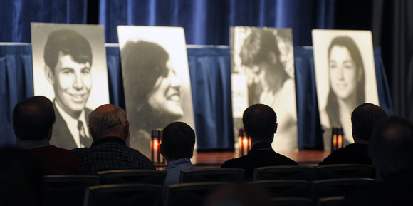 Four men sit staring at a candle-lit stage, on which there are portraits of the four Kent State students who died as a result of the firing by the Guard.