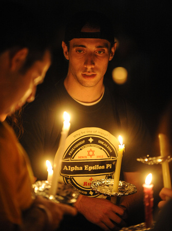 A student holds a candle at night to remember the victims of the May 4th shootings.