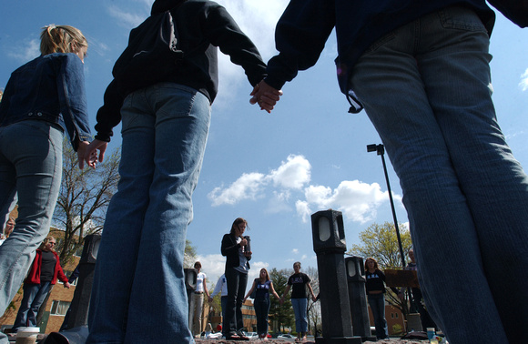 Students gather in a circle, holding hands around a May 4th memorial to remember the victims of the Guard shootings.