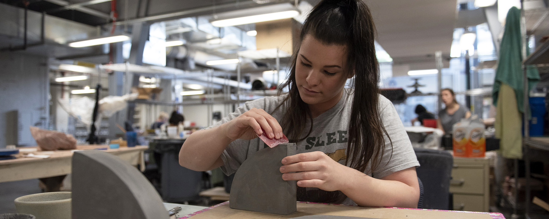 Ceramics graduate student working in studio
