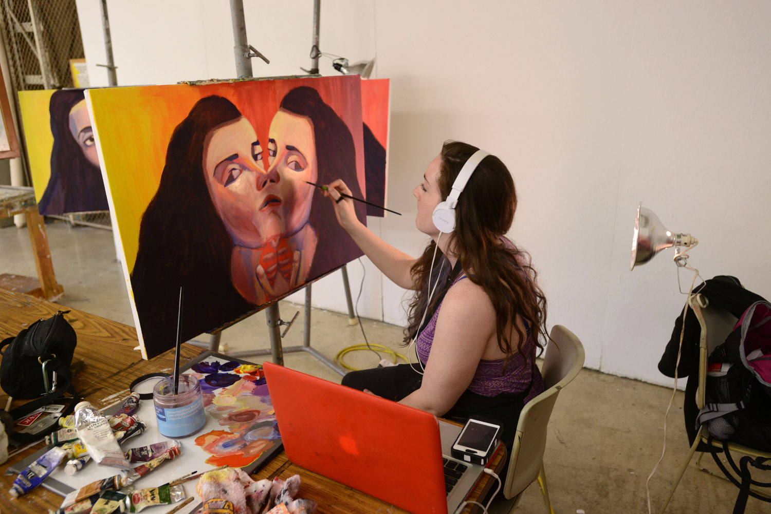 A student, surrounded by her work, paints in her private space in the Art building.