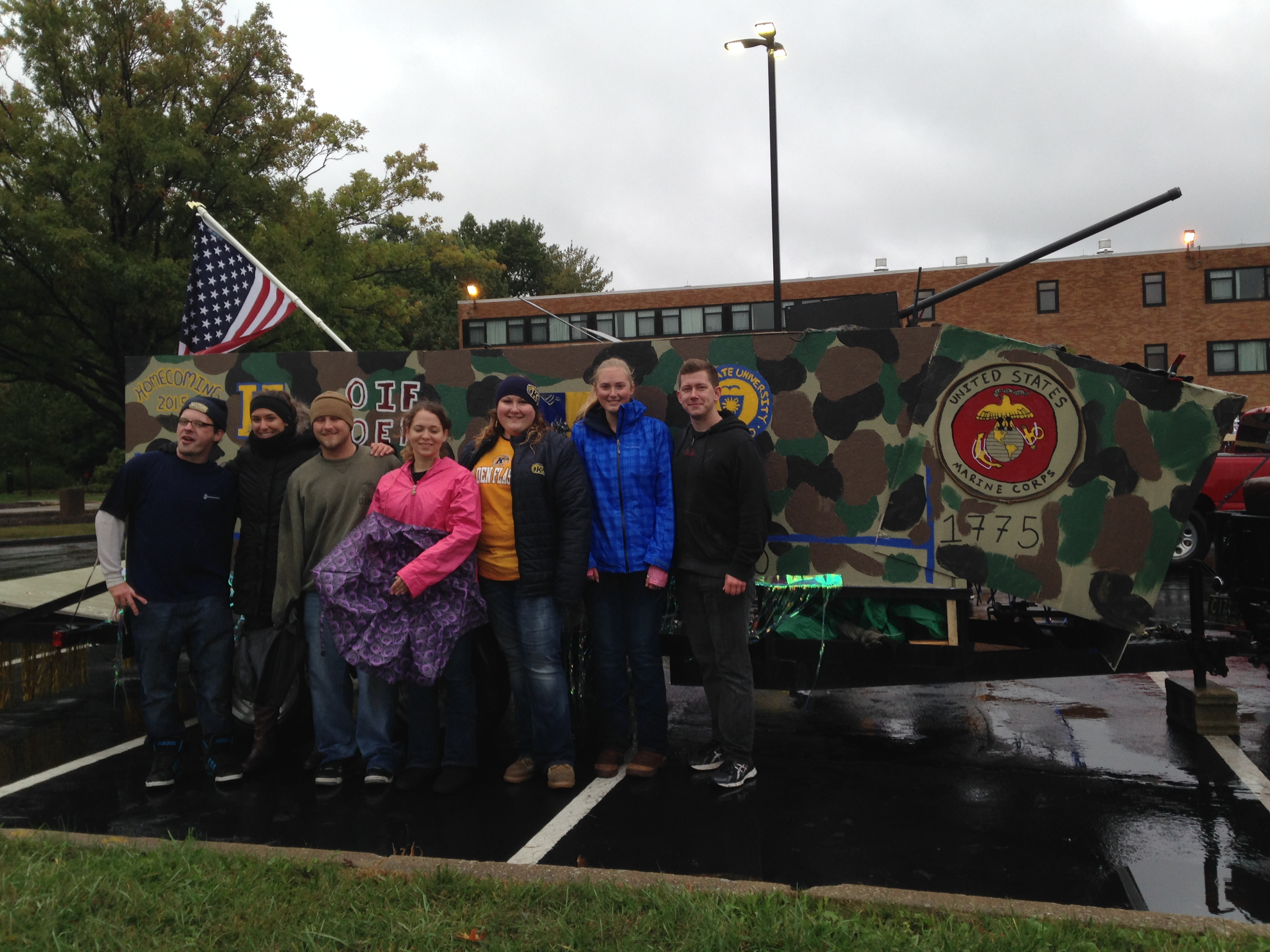 Students of the Veterans Club stand in front of the homecoming float