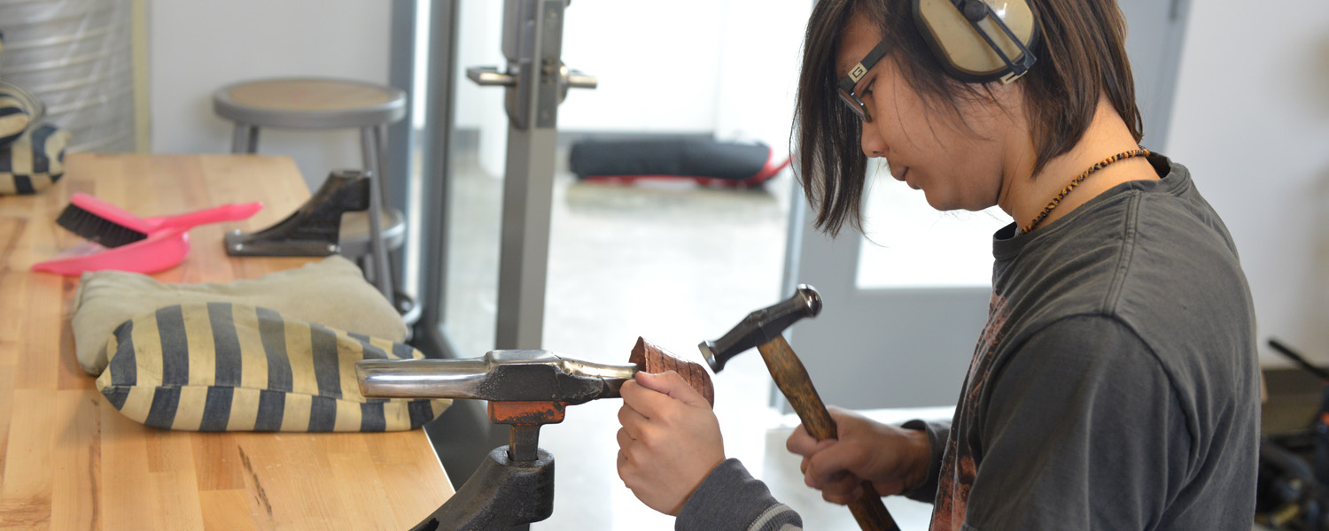 Jewelry/Metals/Enameling student raising a bowl