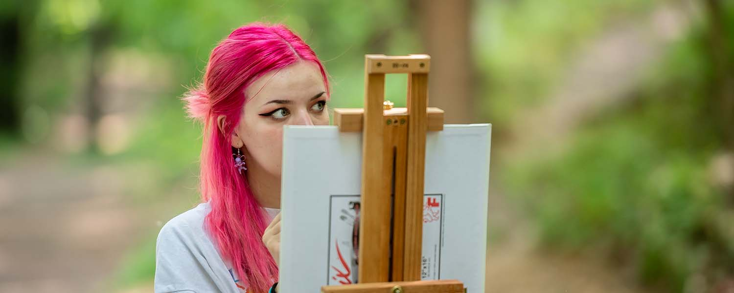 Student painting outdoors