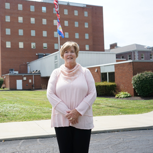 Pat Gless stands near the old Ravenna hospital