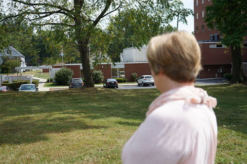 Pat Gless glances at the old Emergency Room parking lot from the former location of her back window