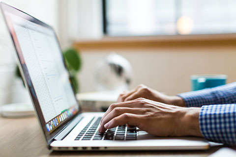 Participant writing at laptop