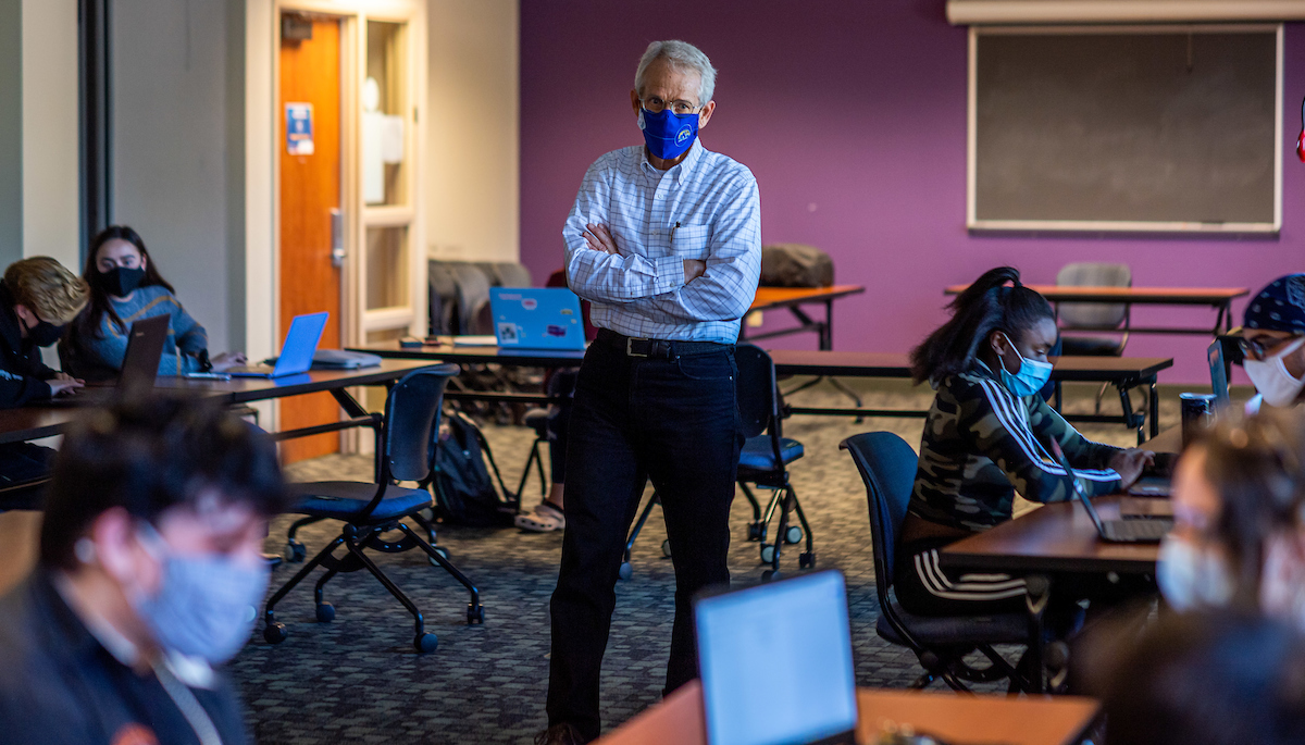 A professor wearing a blue Kent State facial covering stands in a the middle of a classroom of physically distant students at their desks.