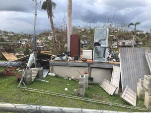 A home destroyed by the storms, with debris scattered around it. It has no roof or walls, just the platform where the foundation stood. All that is left standing is a refrigerator and cabinet. Street light poles are on the ground and on the platform.