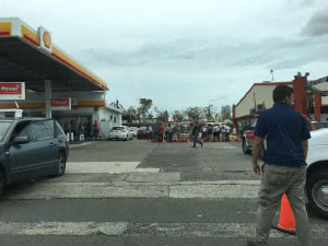 Puerto Rican citizens gather at a fuel station following the storms.