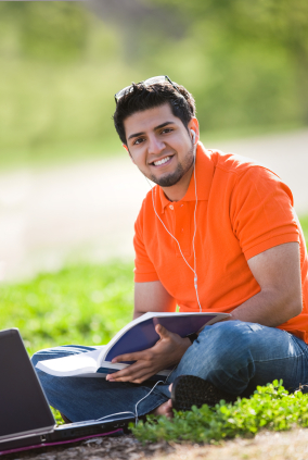 A student wearing headphones listens to a lecture on his laptop outside on a bright sunny day