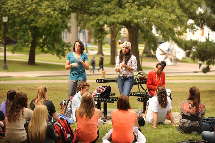 sign language interpreters sign to a group of students sitting outside