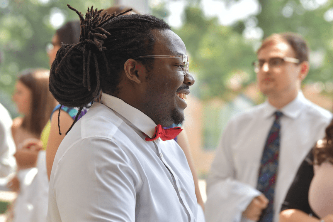 student smiling and laughing at white coat ceremony