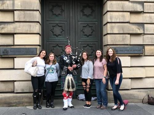Students pose with a bagpiper in Edinburgh, Scottland