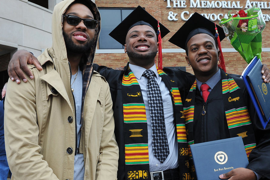 New Kent State graduates pose with family members outside the MAC Center following a Spring 2016 commencement ceremony.
