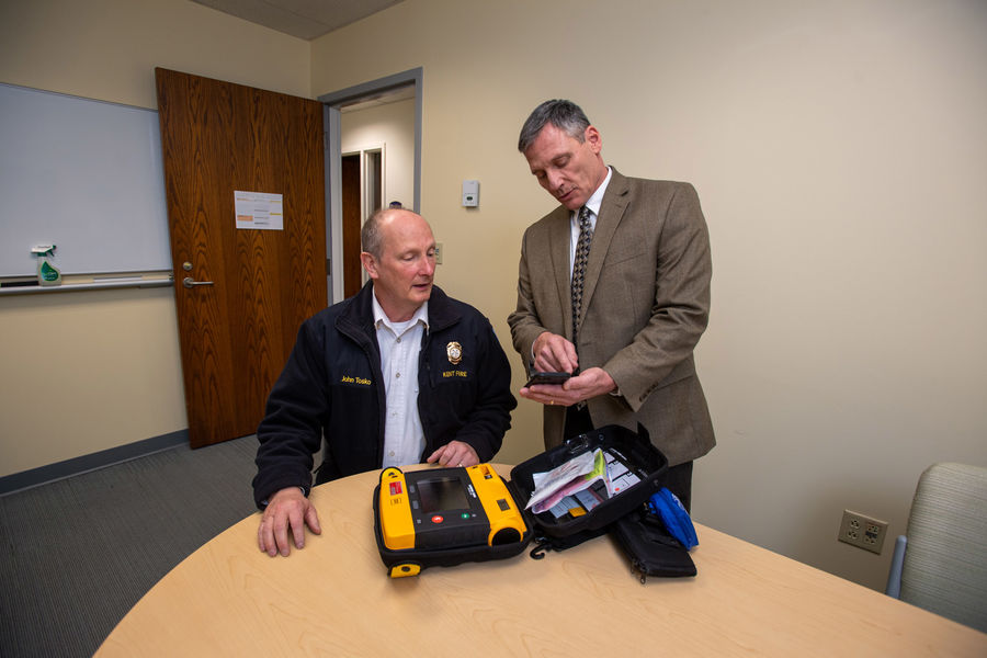 Dean Tondiglia (right), Kent State University police chief and director of public safety, goes through the PulsePoint Respond app on his phone while Kent Fire Chief John Tosko (left) looks on with an automated external defibrillator (AED) in front of him.