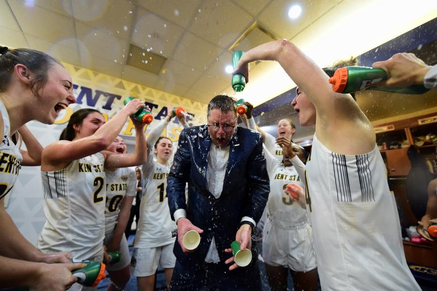 Members of the Kent State University women's basketball team celebrate clinching a share of the 2020 Mid-American Conference East Division championship with head coach Todd Starkey.