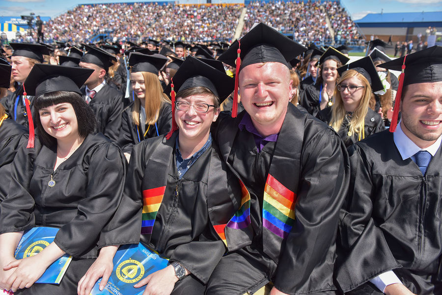Kent State University students wearing their rainbow graduation stoles smile during the university's 2019 One University Commencement.