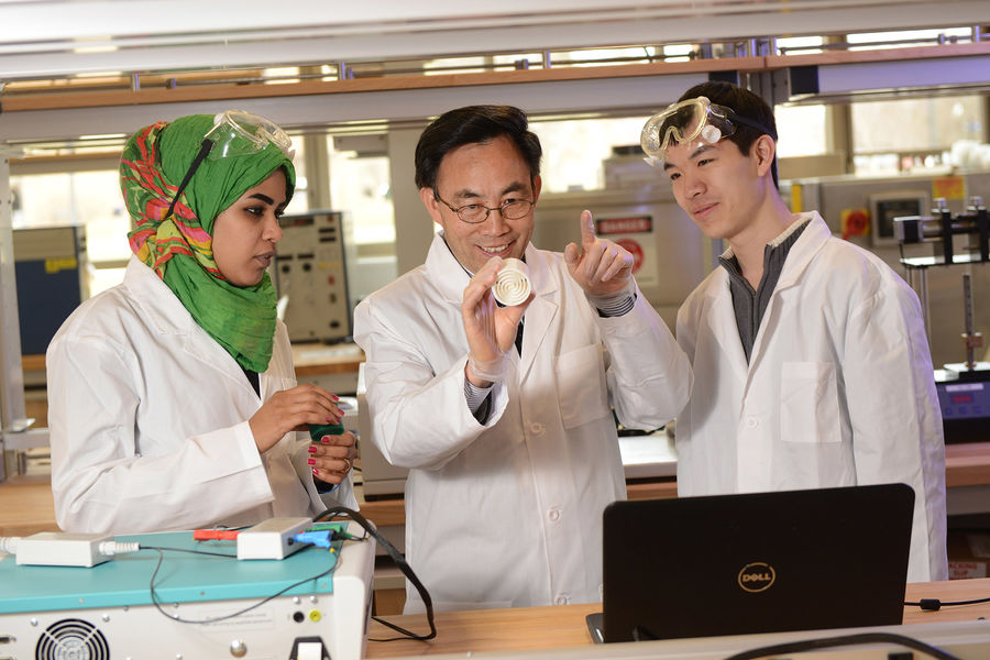 Yanhai Du, Ph.D. (center), assistant professor in Kent State University's College of Applied Engineering, Sustainability and Technology, teaches students about fuel cell technology.