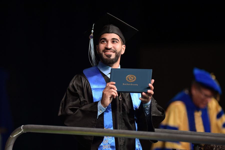 A Kent State University graduate displays his diploma for family and friends during the Summer 2017 Commencement ceremony in the Memorial Athletic and Convocation Center.