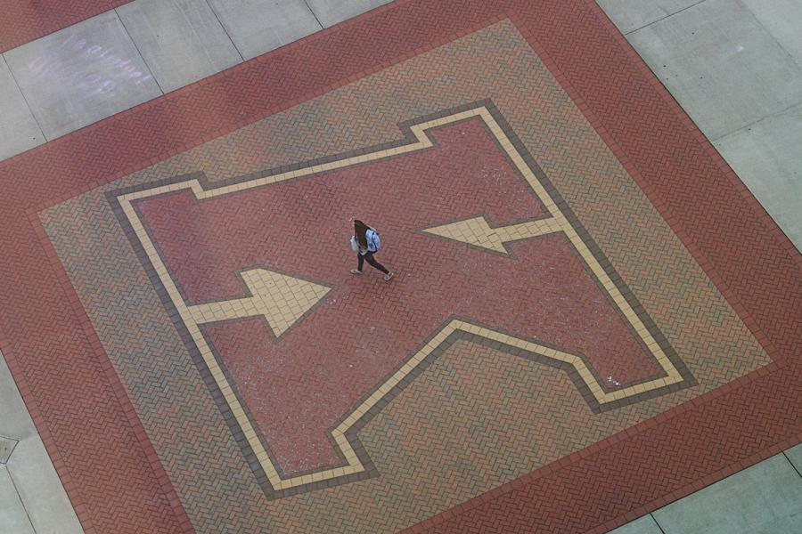 A Kent State University student walks on the K in Risman Plaza.