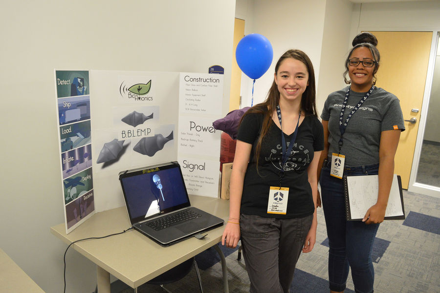 Students pose for a photo while presenting their project during SkyHack, Kent State University's aviation design challenge.