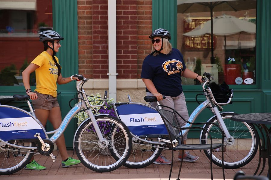 """Two Kent State University students ride Flashfleet bikes in downtown Kent. Kent State was named a Green College in the 2016 Princeton Review's """"Guide to 361 Green Colleges"""" for its focus on environmentally friendly transportation."""