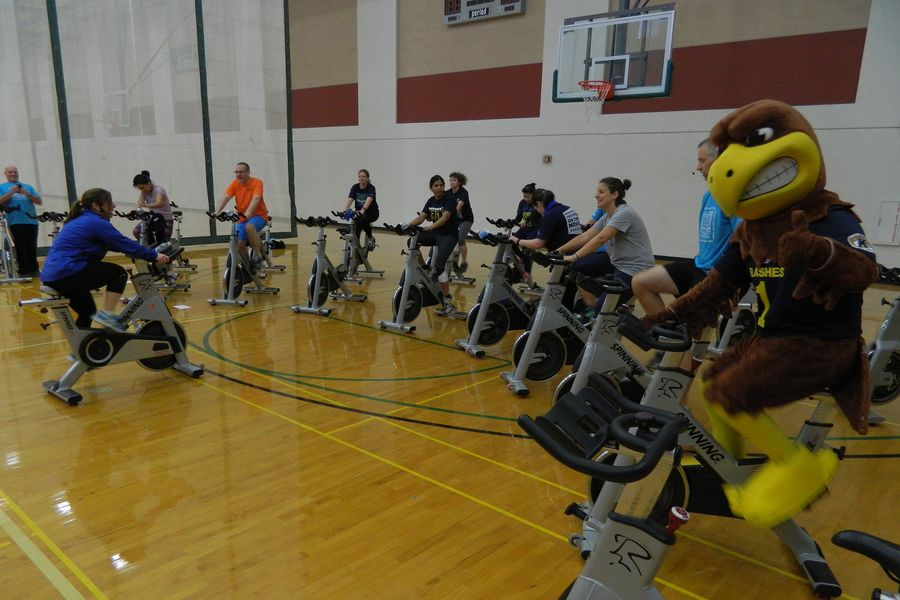 Kent State University employees and Flash, the university mascot, take part in a spinning class. For the third year in a row, the American Heart Association has recognized Kent State for its workplace wellness program.