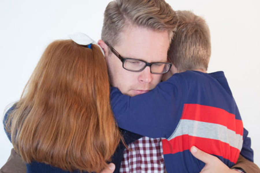 Father hugging children with sad expression