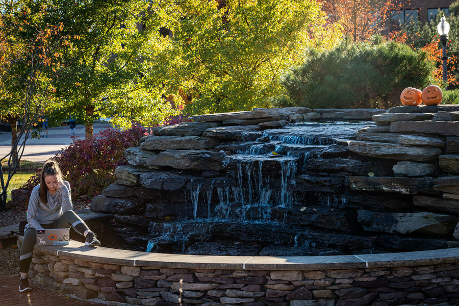 A student finds a serene and festive study spot on the fountain in the Student Memorial Garden near Manchester Field on a mild fall day.