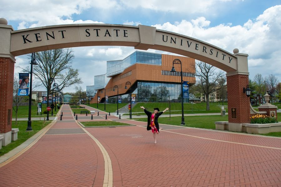 A student poses under the Kent State University archway in her cap and gown as she readies for graduation.