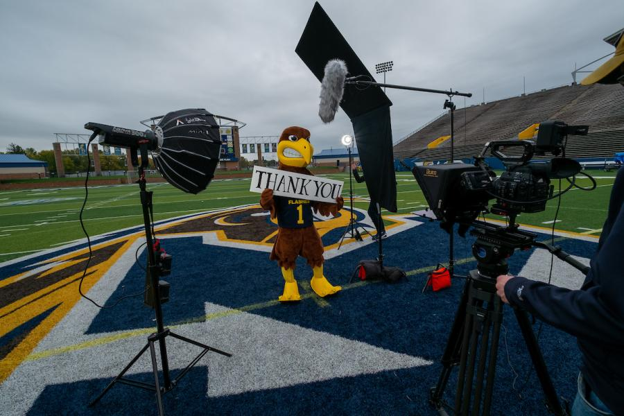 """Kent State's mascot Flash holds a """"Thank You"""" sign while filming a scene for a commercial honoring the university's front line employees."""