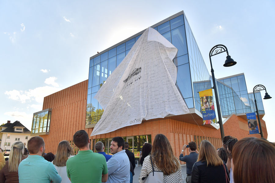 A sheet, signed by Kent State students, employees, alumni and others, is pulled down to reveal the new Center for Architecture and Environmental Design.