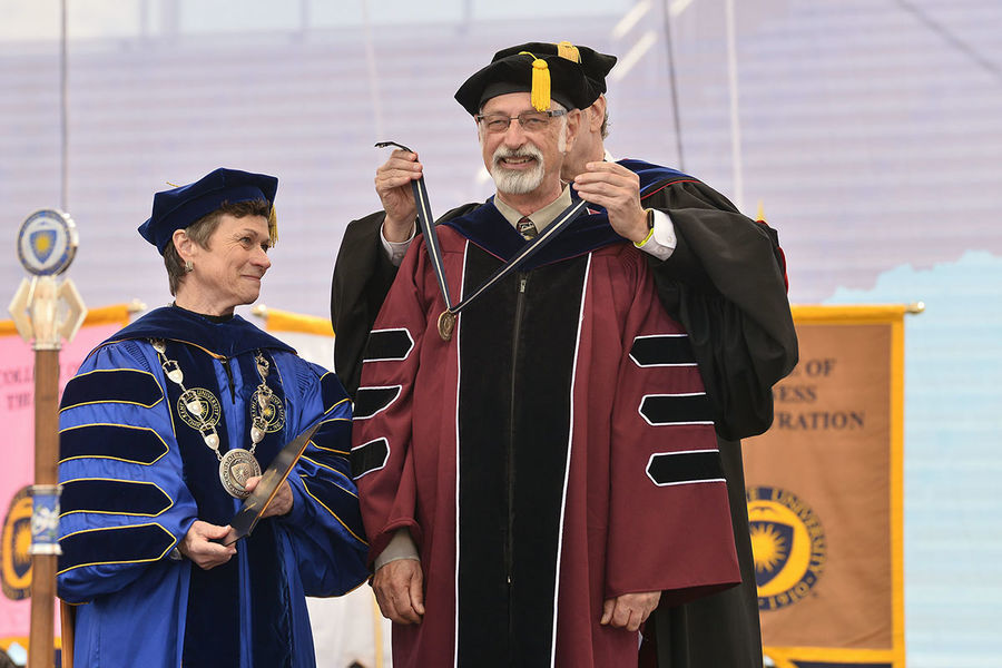 Todd Diacon, Kent State's senior vice president for academic affairs and provost, places the President's Medal on Distinguished Professor of Human Evolutionary Studies C. Owen Lovejoy as Kent State President Beverly Warren watches.