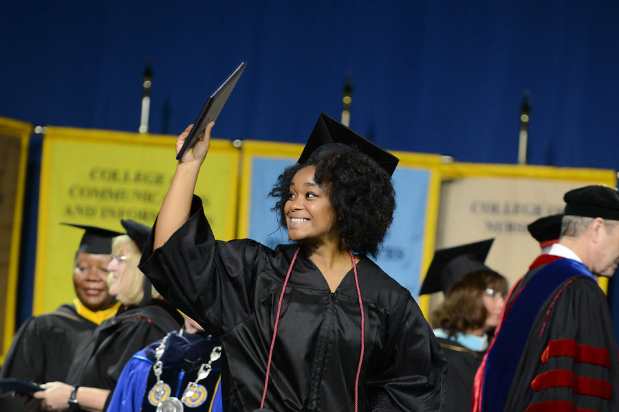 A summer 2015 graduate shows off her diploma during the Commencement ceremony.