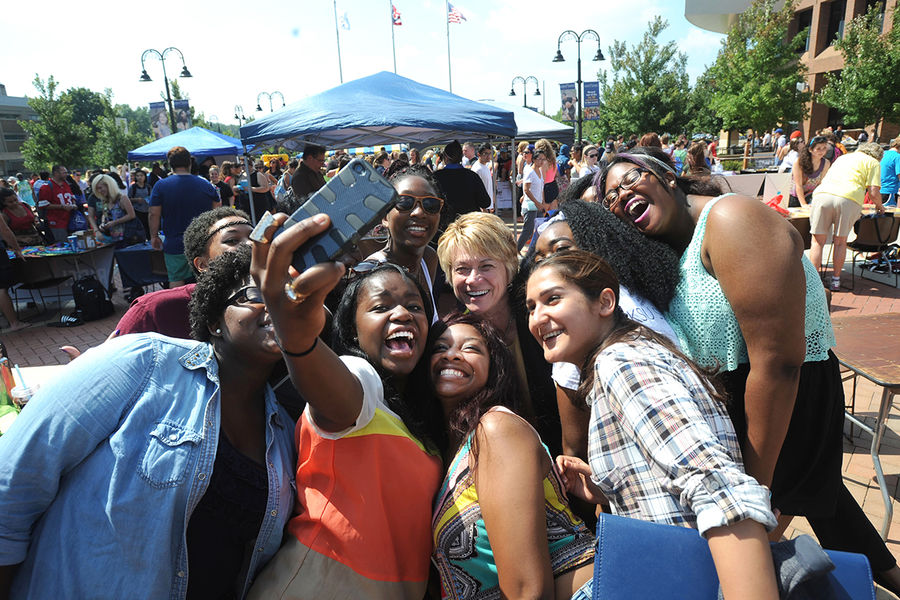 Kent State President Beverly Warren poses for a photo with a group of enthusiastic students in Risman Plaza during the annual Black Squirrel Festival.