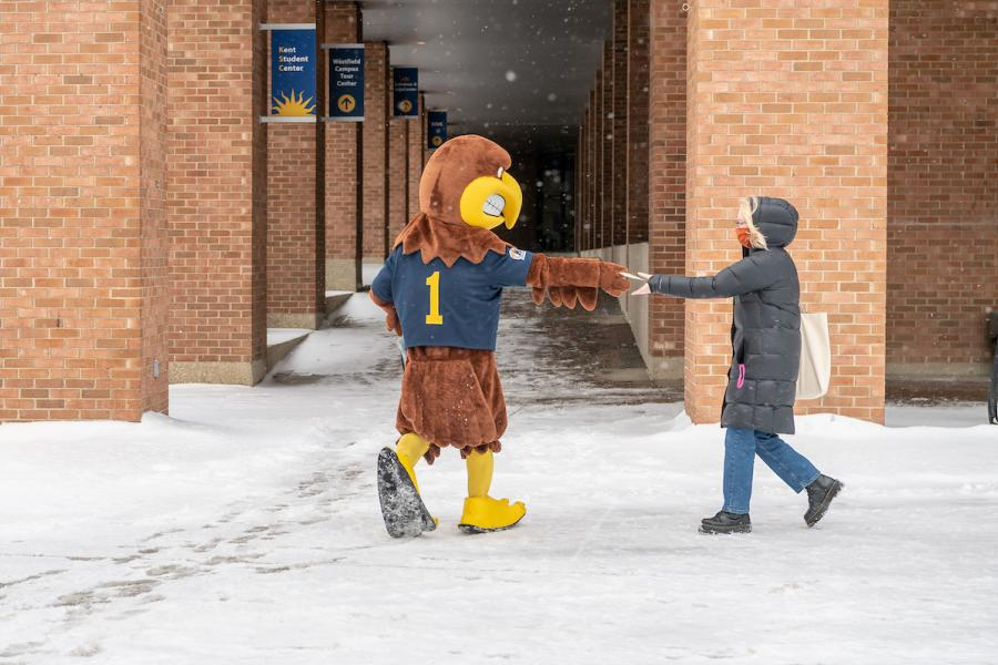 Flash hands a face covering to a student on a snowy day on Kent Campus.