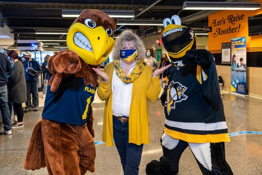 Flash mascot standing with fan wearing face covering
