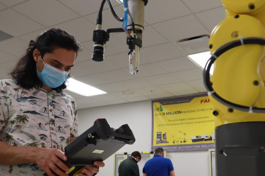 Senior mechatronics major Saroj Dahal working with the FANUC LR Mate 200iD robot