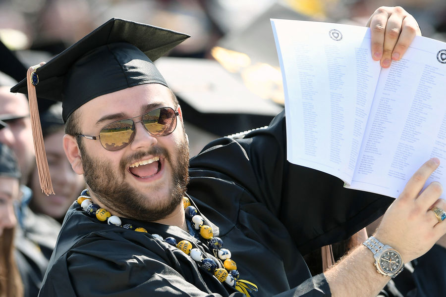 A Kent State graduate indicates to his family, seated in the stands at Dix Stadium, that he has located his name in the 2018 One University Commencement program while waiting for the ceremony to begin.