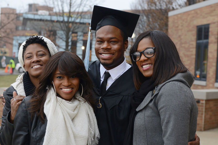 A new Kent State graduate poses with his family before the start of Fall Commencement ceremonies at the Memorial Athletic and Convocation Center.