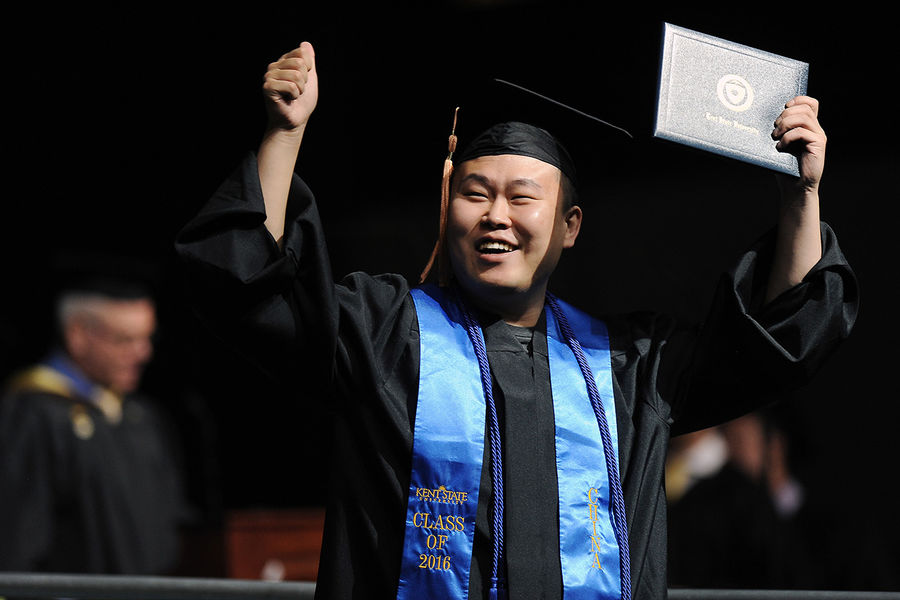 A Kent State graduate celebrates after receiving his diploma during the Summer 2016 Commencement ceremony in the MAC Center.