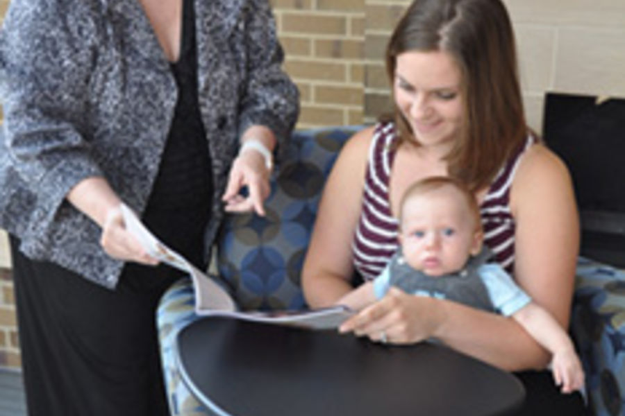 Ruth Ann Mullen reviews breastfeeding information with her student, Leah Wilson, holding her son, Maddox. Wilson is a student in the BSN program at Kent State Salem who is able to use the accommodations provided on campus for breastfeeding moms.