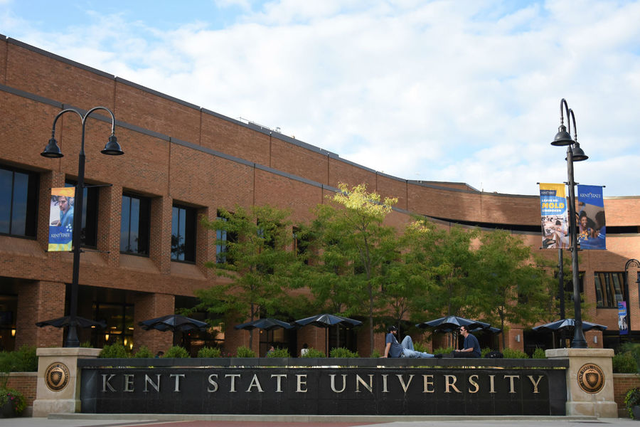Students sit on top of the Kent State University fountain in Risman Plaza.