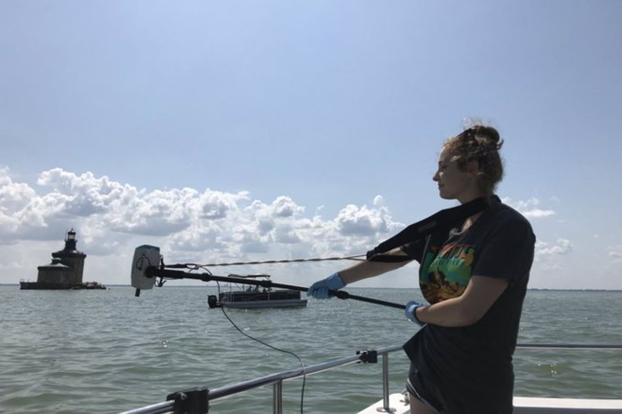 Kent State geology undergraduate student Nicolle Di Domenico positions an ASD Field Spec HH2Pro spectroradiometer over the side of the commercial fishing vessel Reel Deal, the research platform at the Toledo Harbor Lighthouse.