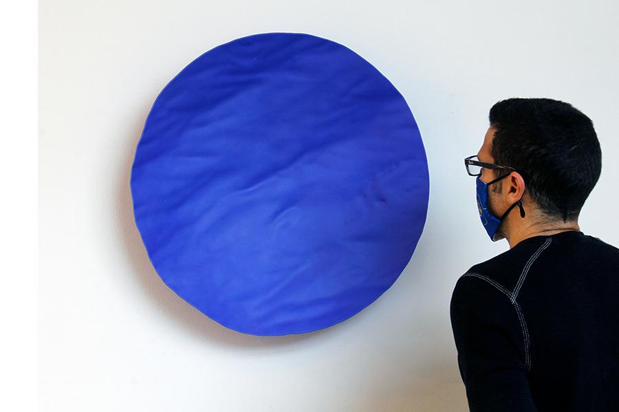 Davin Ebanks standing in front of his glass sculpture, a circular glass shape that has realistic water ripples texturing the surface