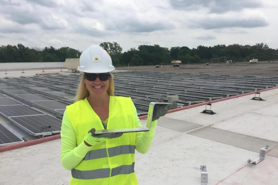 Kent State Alum Emilie O'Leary on rooftop with solar panels